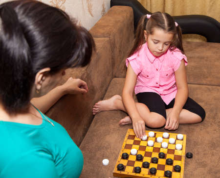 draughts: little girl in pink shirt and black trousers playing draughts with her mother at home