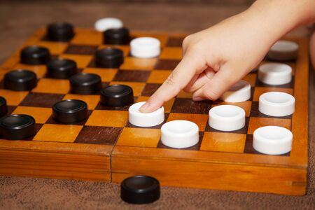 draught: childs hand moves the white piece to the chessboard