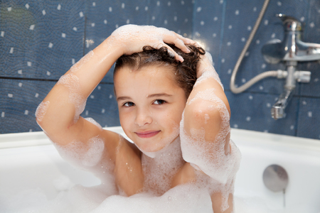 shampooing: little girl washes her head in the bath closeup