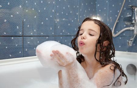 baÑo: niña jugando con pompas de jabón en el baño Foto de archivo