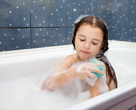little girl washing her hand with sponge sitting in the bath closeup