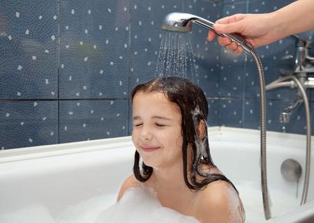 personas banandose: la mano de la madre vierte una ni�a fuera de la ducha en el ba�o primer plano Foto de archivo