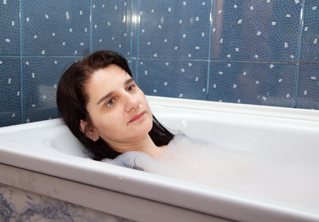 lying in bathtub: young brunette woman lying in a bathtub closeup
