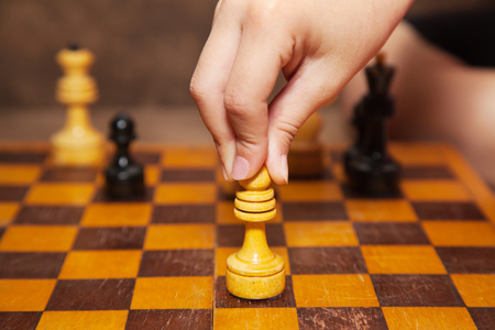 chess piece: childs hand holding a chess piece Stock Photo