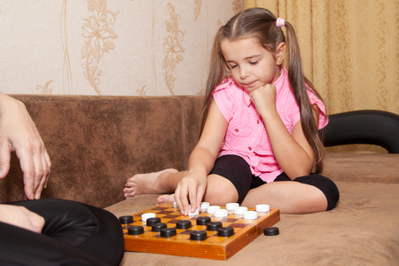draughts: little girl playing draughts with her mother at home