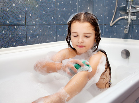 little girl washing her hand sitting in the bath