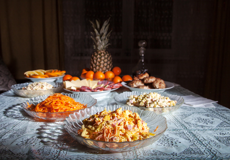 festively: festively laid table with salads, pineapple, meat, wine and  tangerines at night Stock Photo