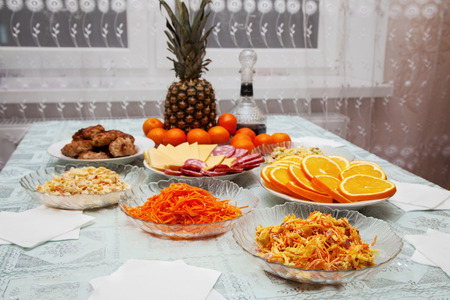 festively: festively laid table with salads, pineapple, meat, wine and  tangerines