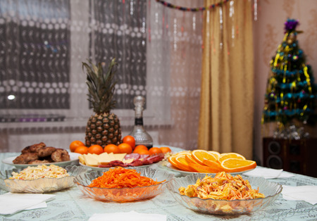festively: festively laid table with salads, pineapple and  tangerines Stock Photo