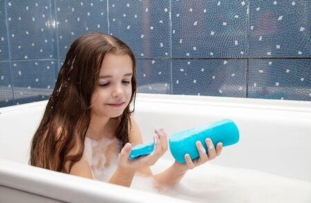 bath: little smiling girl with long brown hair taking a bath with a blue sponge Stock Photo
