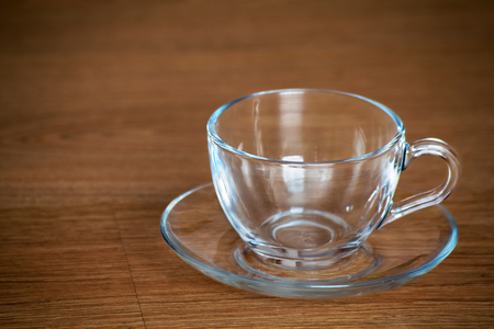 glass cup and saucer on wooden table closeup Stock Photo