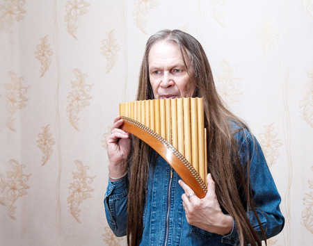 pan flute: long-haired elderly man playing the pan flute closeup