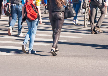 pedestrians walking on a crosswalk outside on sunny spring day Stock Photo