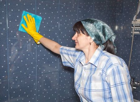 bathroom tile: young smiling woman washes a tile in the bathroom closeup Stock Photo