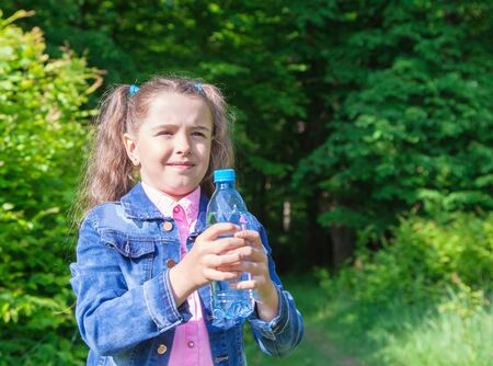 denim jacket: girl in a denim jacket holding a water bottle outdoor closeup Stock Photo