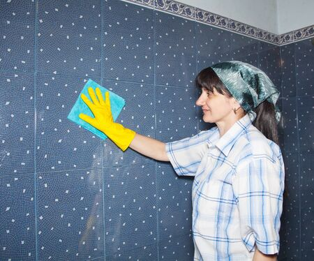 bathroom tile: young smiling woman washes a tile in the bathroom