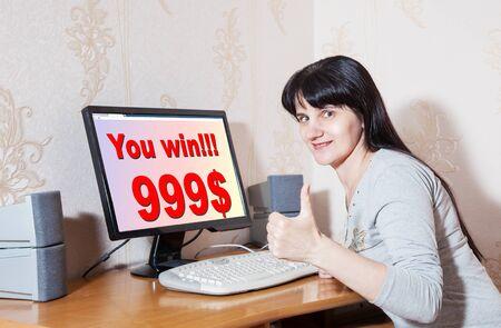 exult: young brunette woman rejoices win $ 999 Stock Photo