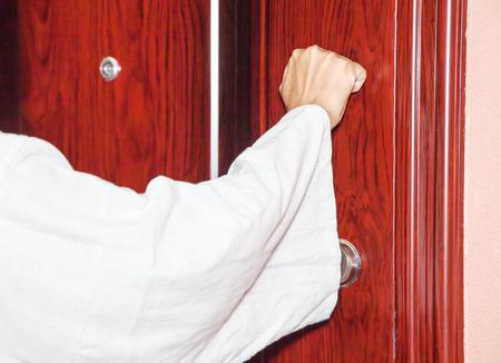 mans hand knocking on the door closeup