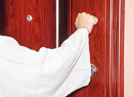 man's hand knocking on the door closeup Standard-Bild