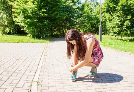 mujer joven que abotona el zapato en la acera el día de verano