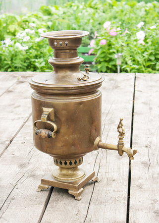 antiquarian: brass old samovar on a wooden table closeup outdoor