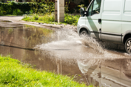 residental: white commercial vehicle riding on big puddle on the road in residental area on sunny summer day closeup