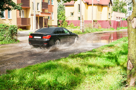 residental: black car riding on big puddle on the road in residental area on summer day