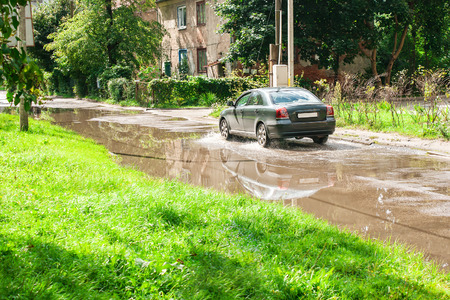 residental: black car riding on big puddle on the road in residental area on sunny summer day Stock Photo