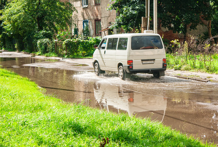 residental: white minibus riding on big puddle on the road in residental area on sunny summer day