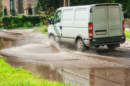 residental: white commercial vehicle riding on big puddle on the road in residental area on summer day