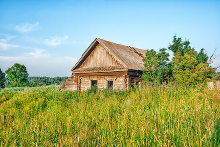damaged roof: old abandoned wooden house on sunny summer day