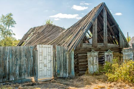 damaged roof: old abandoned destroyed wooden house on summer day