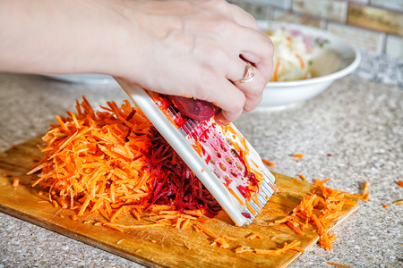 woman cooks the beets with carrot on a grater hands closeup