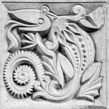 fabulous lizard, a retro stone bas-relief on the wall