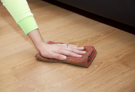neatness: womans hand cleaning the wooden floor with a brown floorcloth closeup