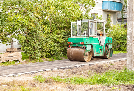 steam roller: roller rolling new asphalt on the pavement outdoor on summer day Stock Photo