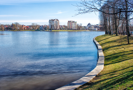 promenade near the lake in the city on sunny spring day