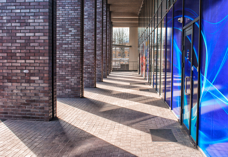 corridor of brick columns in a modern building outdoor on sunny day Stock Photo