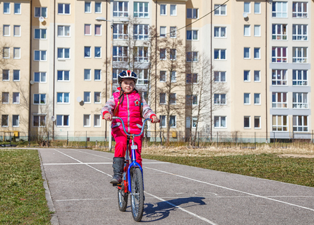 little girl in a red suit and a safety helmet riding a bicycle