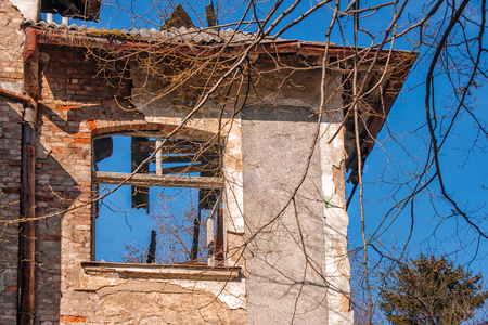 broken window in an abandoned house on sunny spring day closeup