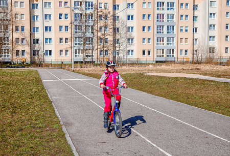 little girl in a red suit and a safety helmet riding a blue bicycle