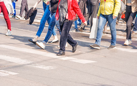 feet of the people going on the street on sunny spring day