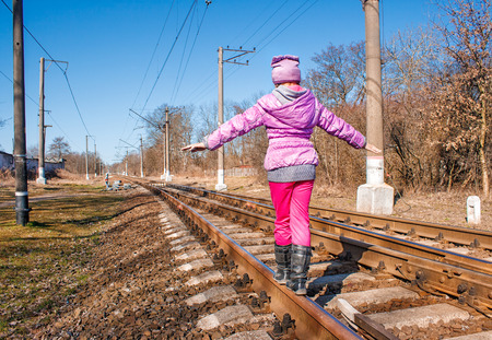 little girl in a red suit walking on rails on sunny spring day