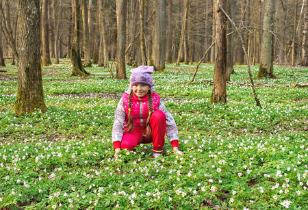 beautiful little girl with wild white flowers in forest on sunny spring day closeup