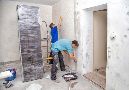 two men applying wallpaper on wall in new home Stock Photo