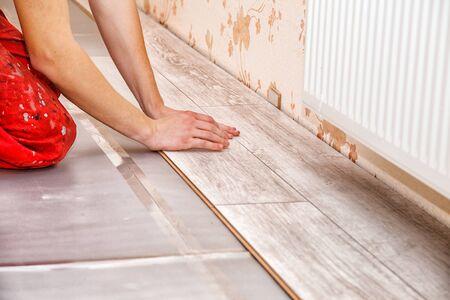 young handyman installing wooden floor in new house, hands closeup Stock Photo