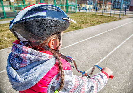 little girl in a red suit and a safety helmet riding a bicycle closeup Stock Photo