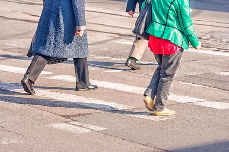women feet, crossing an urban street on sunny spring day Stock Photo