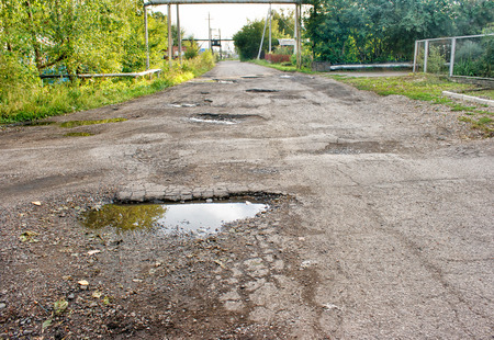 old broken road in the village on sunny summer day Stock Photo