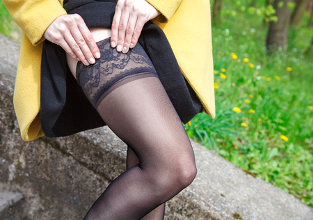 young woman adjusting her stocking standing on the stairs outdoor closeup 版權商用圖片